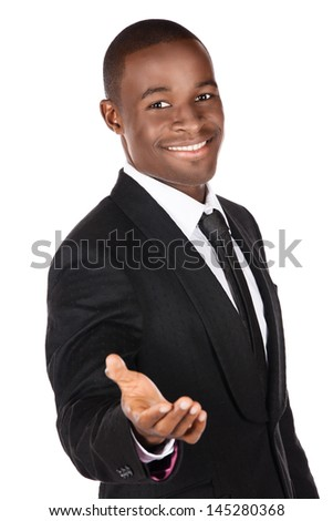 Handsome young successful african businessman wearing a formal black suit, tie and white shirt. He is holding out his hand for a handshake and is smiling at the camera. - stock photo