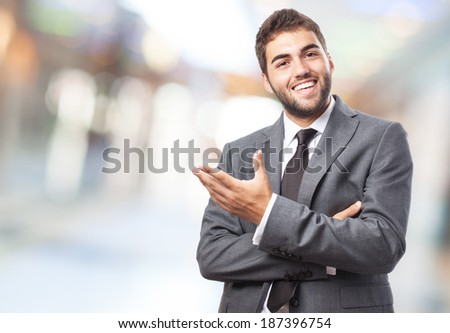 handsome young successful man doing a welcome gesture - stock photo