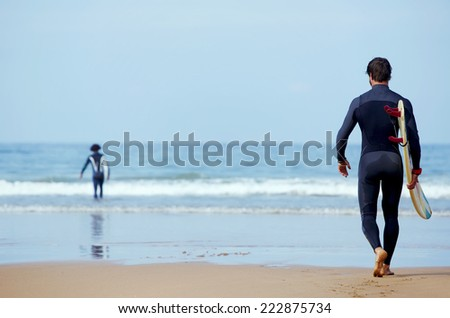 Handsome young surfer man walking at ocean beach holding his surfing board, muscular build surfer carrying surfboard while walking on the beach, men ready to surfing walk on the sand holding board - stock photo