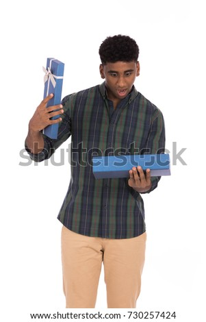 Handsome young surprised man opening gift box, guy wearing caro shirt and beige pants, isolated on white background