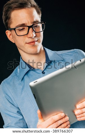 Handsome young tattoed man with tablet pc. He is wering blue shirt. Black background