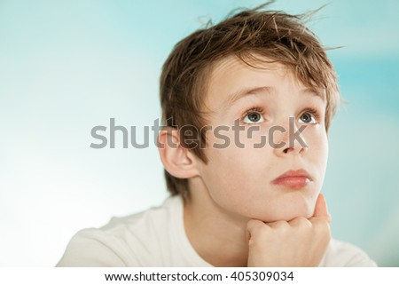Handsome young teenage boy lost in thought resting his chin on his hands looking up with a meditative solemn expression - stock photo