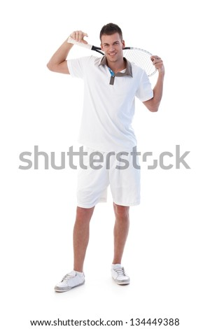 Handsome young tennis player posing with tennis racket in hand, smiling. - stock photo