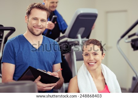 Handsome young trainer with a pretty girl at the gym working out together ion the equipment as he monitors her progress