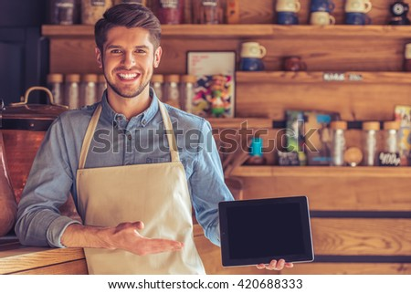 Handsome young waiter in apron is showing a tablet, looking at camera and smiling while standing in the cafe