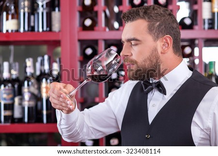 Handsome young wine waiter is tasting red wine. He is holding a glass of wine and smelling it. His eyes are closed with enjoyment. The man is standing in cellar - stock photo