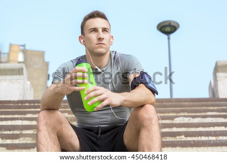 Handsome yung man in sports uniform is holding a bottle of water, resting during morning run - stock photo