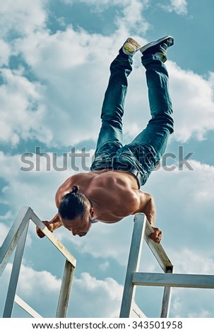 Handstand yoga pose by man on the sky background - stock photo