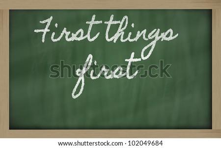 handwriting blackboard writings - First things first - stock photo