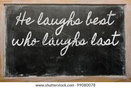 handwriting blackboard writings - He laughs best who laughs last - stock photo