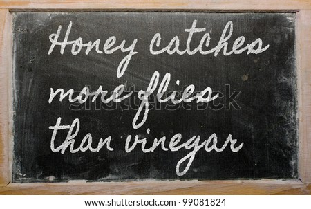 handwriting blackboard writings - Honey catches more flies than vinegar - stock photo