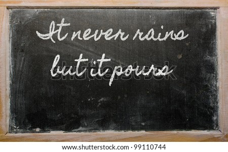 handwriting blackboard writings - It never rains but it pours - stock photo
