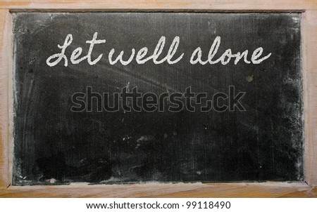 handwriting blackboard writings - Let well alone - stock photo