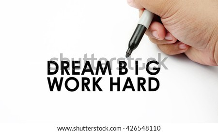 "Handwriting "" dream big work hard "" with the hand and pen isolated in white background."
