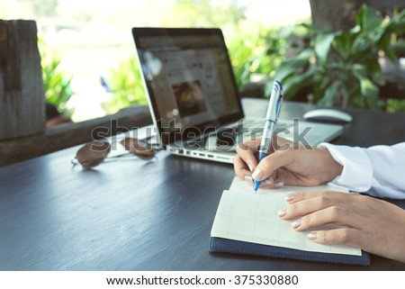 Handwriting, hand writes a pen in a notebook,Vintage tone and soft focus.  - stock photo