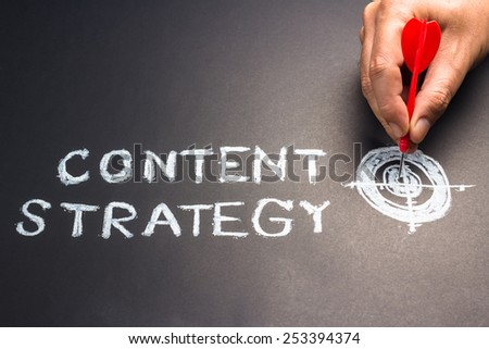 Handwriting of content strategy topic with hand put a dart hit on the target - stock photo