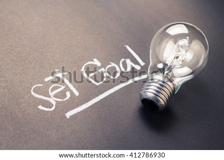 Handwriting of Set Goal text with glowing light bulb - stock photo