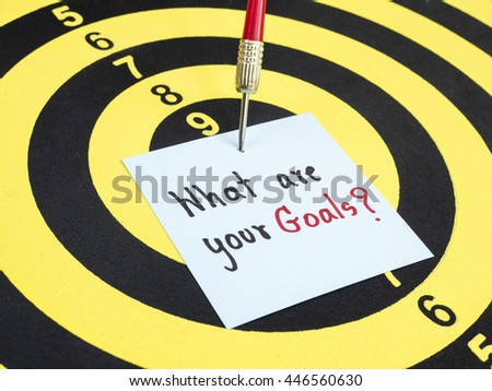 Handwriting What are your goal on notepaper with dart arrow and dart board. - stock photo