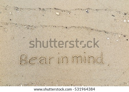 "Handwriting words ""Bear in mind"" on sand of beach"