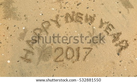 "Handwriting words ""HAPPY NEW YEAR 2017"" on sand of beach"