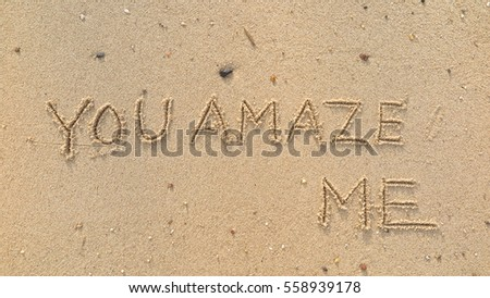 "Handwriting words ""YOU AMAZE ME"" on sand of beach"