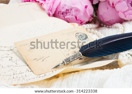 Handwritten antique letter   and blue feather pen on white lace background