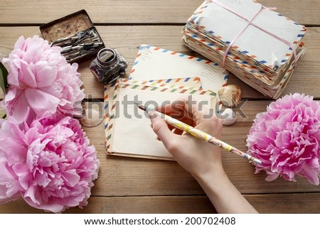 Handwritten letters and bouquet of pink peonies - stock photo