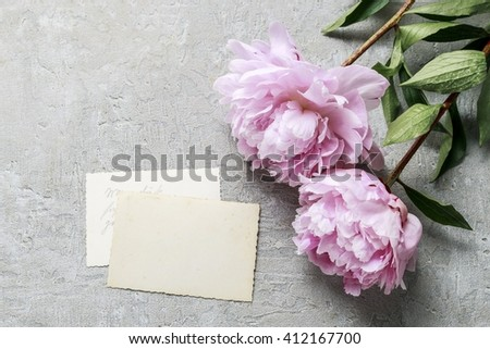 Handwritten letters and pink peonies on grey background, copy space - stock photo