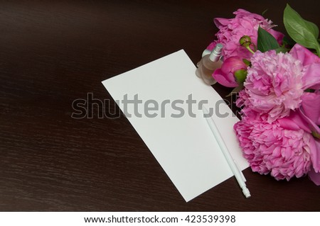 Handwritten letters, perfume and pink peonies on dark wooden background, copy space