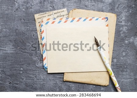 Handwritten letters, vintage pen and envelope on gray background, copy space - stock photo