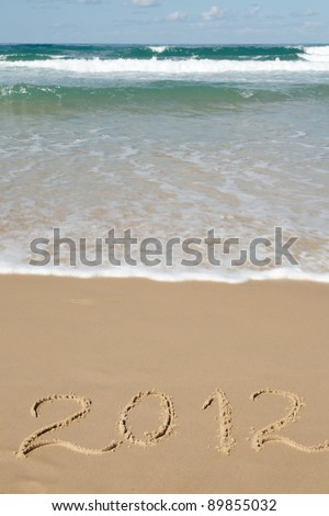 Handwritten message for year 2012 on deserted beach leaves room in clean sand - stock photo