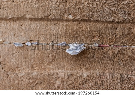 handwritten prayers tucked in cracks in the ancient Western Wall, Jerusalem, Israel - holy site in Judaism as the outside wall for the Second Temple - stock photo