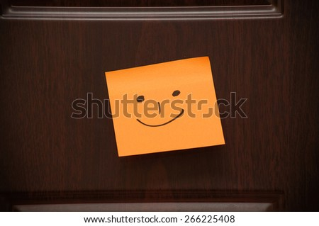 Handwritten Smile on the sticky note on the wooden door - stock photo