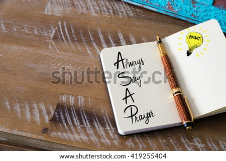 Handwritten text ASAP Always Say A Prayer with fountain pen on notebook. Concept image with copy space available. - stock photo