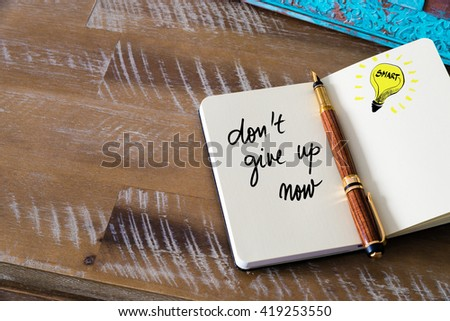 Handwritten text Don't Give Up Now with fountain pen on notebook. Concept image with copy space available. - stock photo