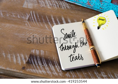 Handwritten text Smile Through The Tears with fountain pen on notebook. Concept image with copy space available. - stock photo
