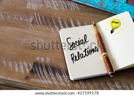 Handwritten text Social Relations with fountain pen on notebook. Concept image with copy space available. - stock photo