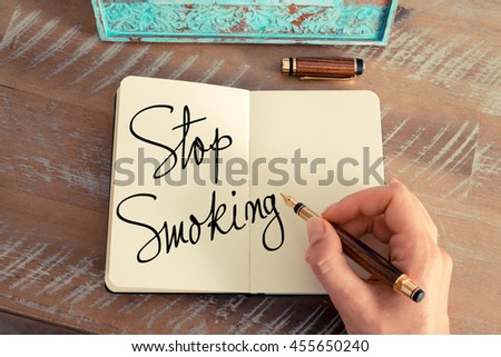 Handwritten text Stop Smoking as business image. Retro effect and toned image of a woman hand writing a note with fountain pen on a notebook. - stock photo