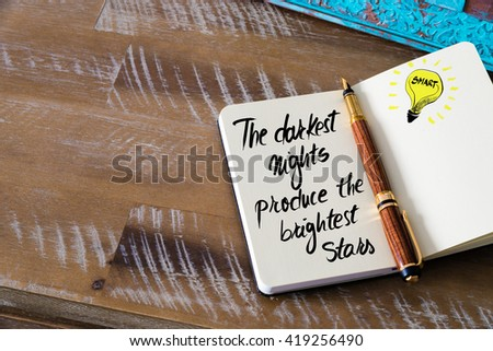 Handwritten text The darkest nights produce the brightest stars with fountain pen on notebook. Concept image with copy space available. - stock photo