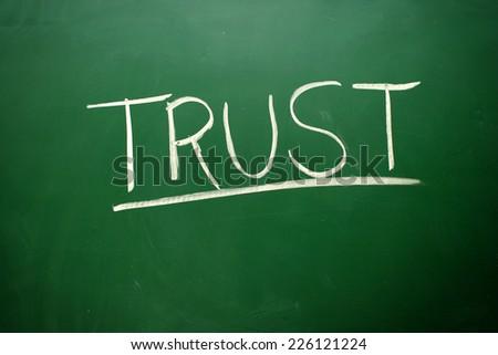 Handwritten Trust word with white chalk on a blackboard - stock photo