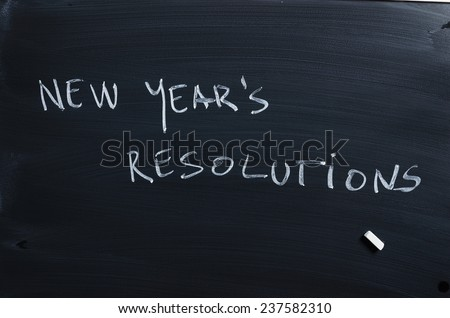 "Handwritten word: ""New Year's Resolutions"" over black chalkboard"