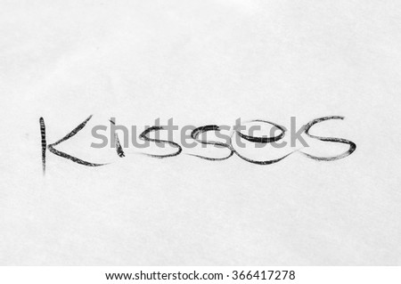 "Handwritten word of ""kisses"" with black on a white paper"