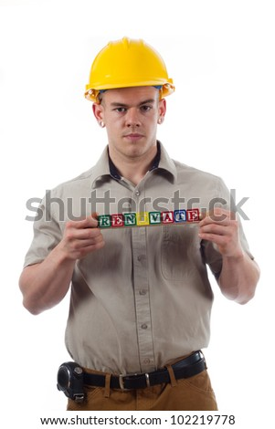 "Handy Man holds childrens building blocks that spell ""Renovate"" - stock photo"