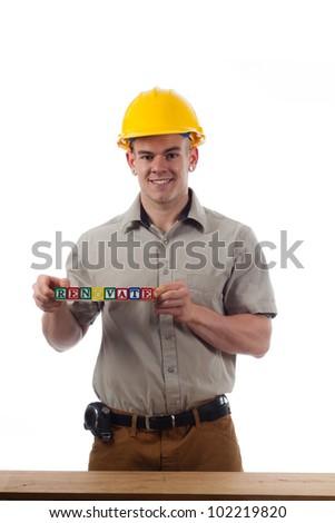 "Handy Man holds childrens building blocks that spell ""Renovate"" - stock photo"