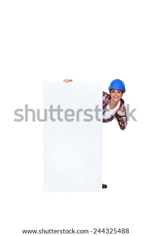 Handy-woman stood by blank marketing panel