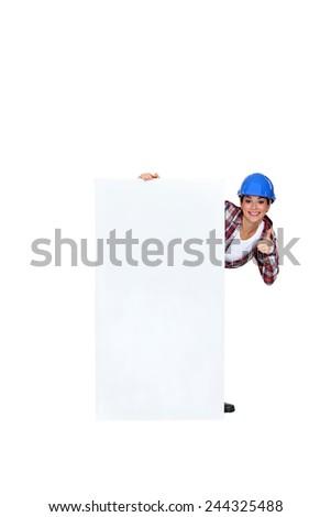 Handy-woman stood by blank marketing panel - stock photo