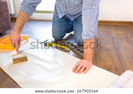 Handyman applying blue for a wallpaper - stock photo