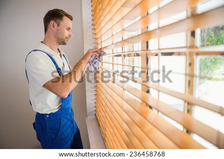Handyman cleaning blinds with a towel in a new house - stock photo