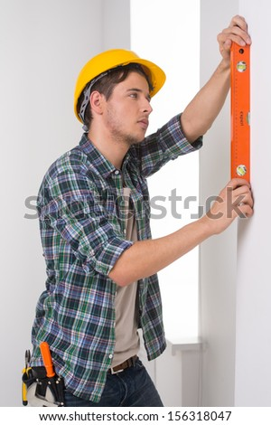Handyman. Confident craftsperson in hardhat measuring the wall level