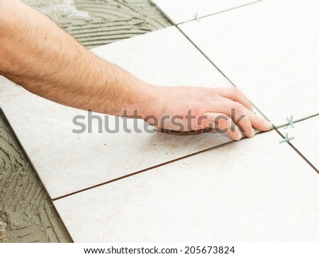 Handyman doing renovation works - floor tiling. - stock photo
